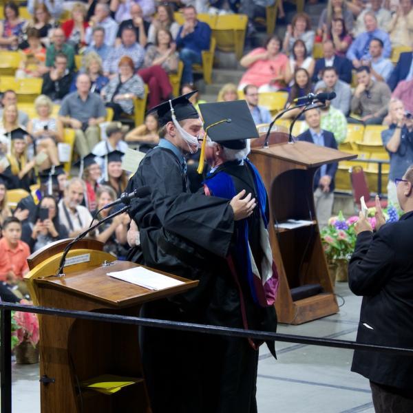 Emcee Lew Harvey embraces his son, Sebastian, the psychology graduate