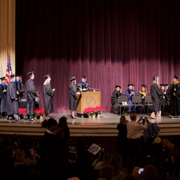 The undergraduates cross the stage for a diploma (cover), handshake, and photo op