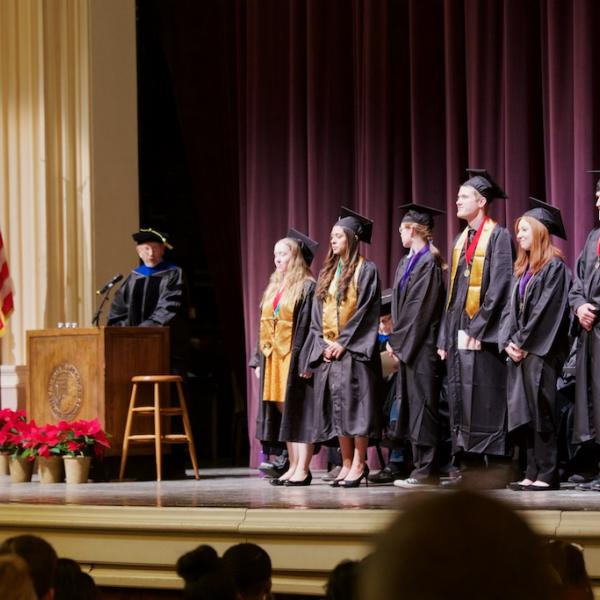Professor Dick Olson presents the students graduating with Latin Honors