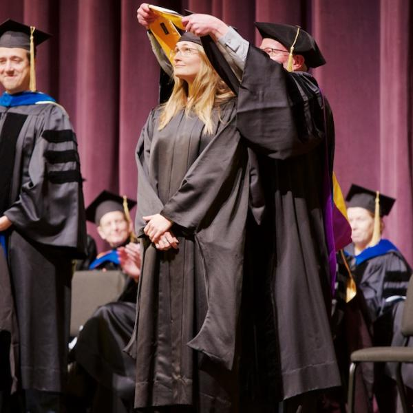 Clinical student Natasha Hansen is given her Master's hood by Professor Mark Whisman