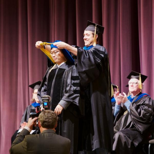 Cognitive student Wani Woo is hooded by his PhD advisor Professor Tor Wager