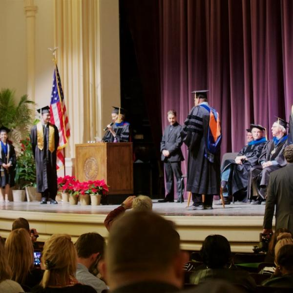 The students cross the stage to get a marble, a diploma cover, and a handshake