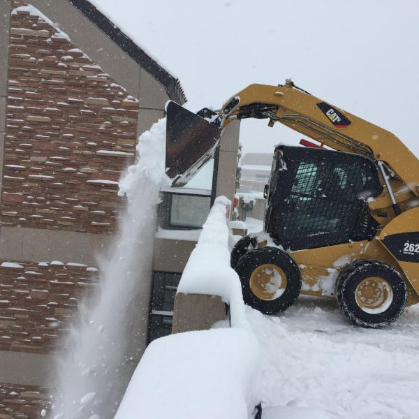 Bobcat plow dumping snow off the roof of Regent Parking Garage after a heavy snowfall