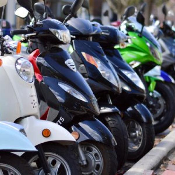 A row of mopeds lined up in a campus motorcycle parking lot