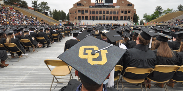 Close up photo of student with CU on their graduation cap during commencement speech