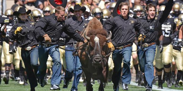 Picture of Ralphie and the Ralphie handlers running on Folsom Field.