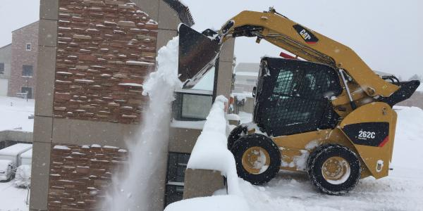 Snow removal in a parking lot on campus