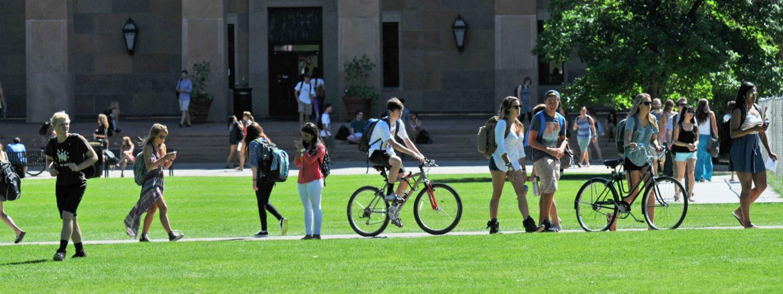 A biker among a lot of pedestrians in front of Norlin.