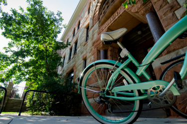 Close up photo of green bike parked in front of Woodbury building on CU Boulder campus.