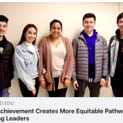 Five students stand against hallway wall smiling.