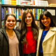 three people stand in front of a bookshelf and smile