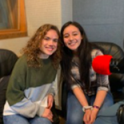 two people sit in front of a mic and smile