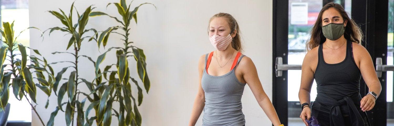 two women walking into the rec wearing masks