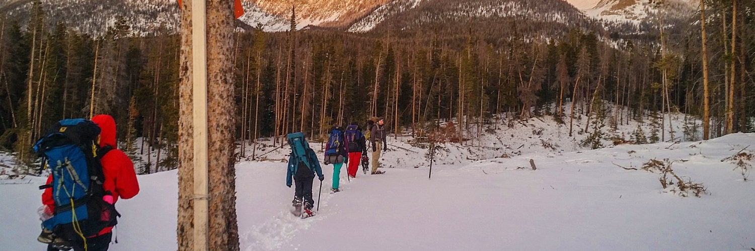 Group snowshoeing past a yurt