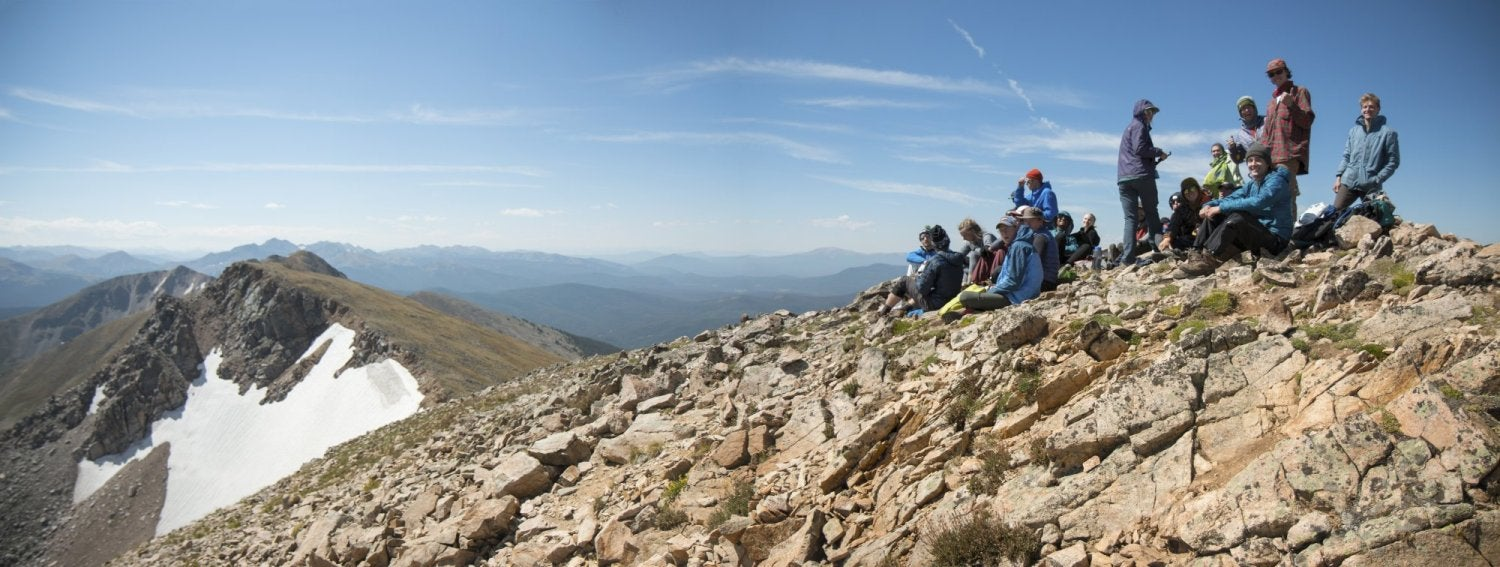 Students sitting on top of a 14er looking at the views.