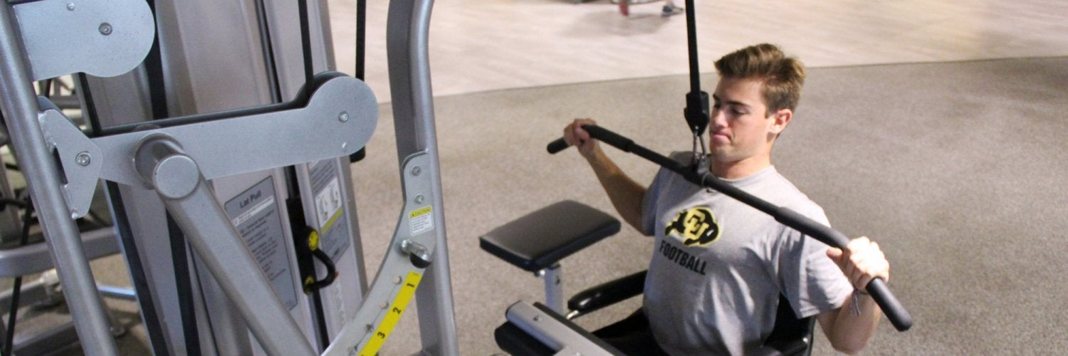 Student using adaptive equipment at rec center