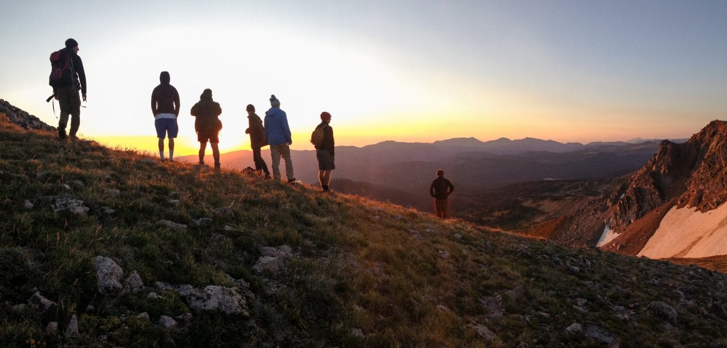 Students on top of a mountain at sunset