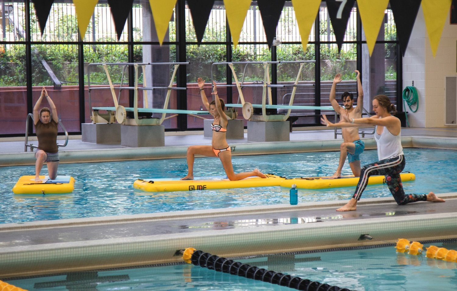 students on paddleboards in the pool doing a downward yoga poses