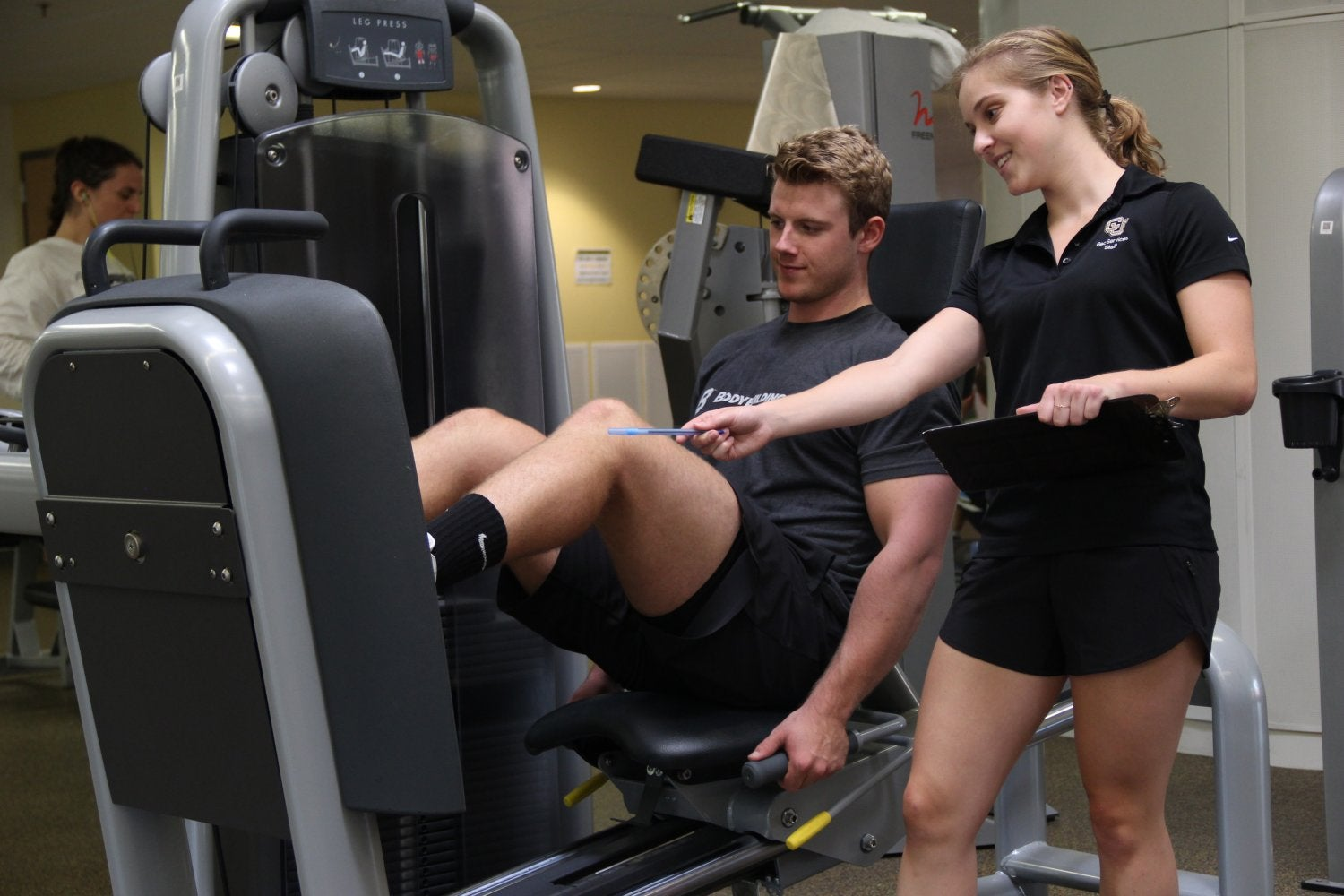 a personal trainer working with a student