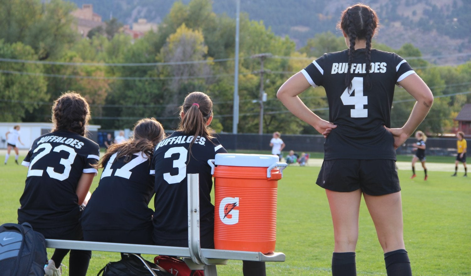 the back of four women's soccer players on the sideline during a game