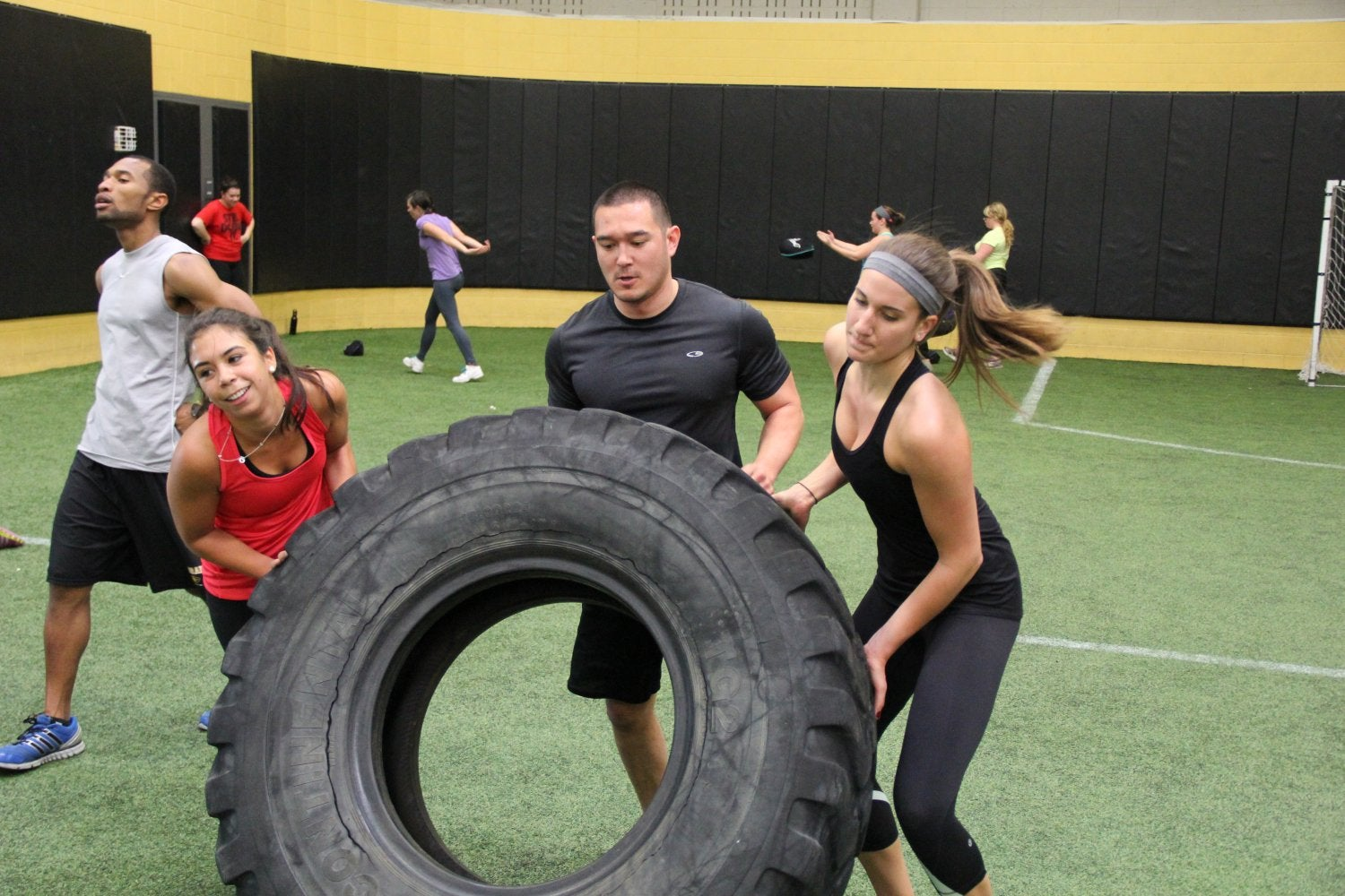 a few students working together to turn over a tire