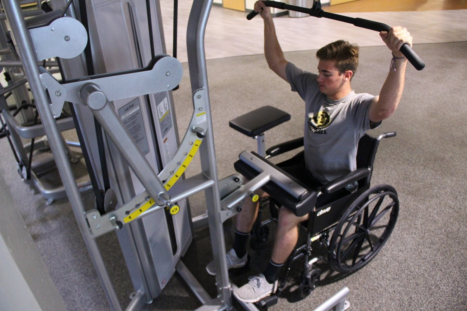 student in a wheelchair using weightlifting equipment