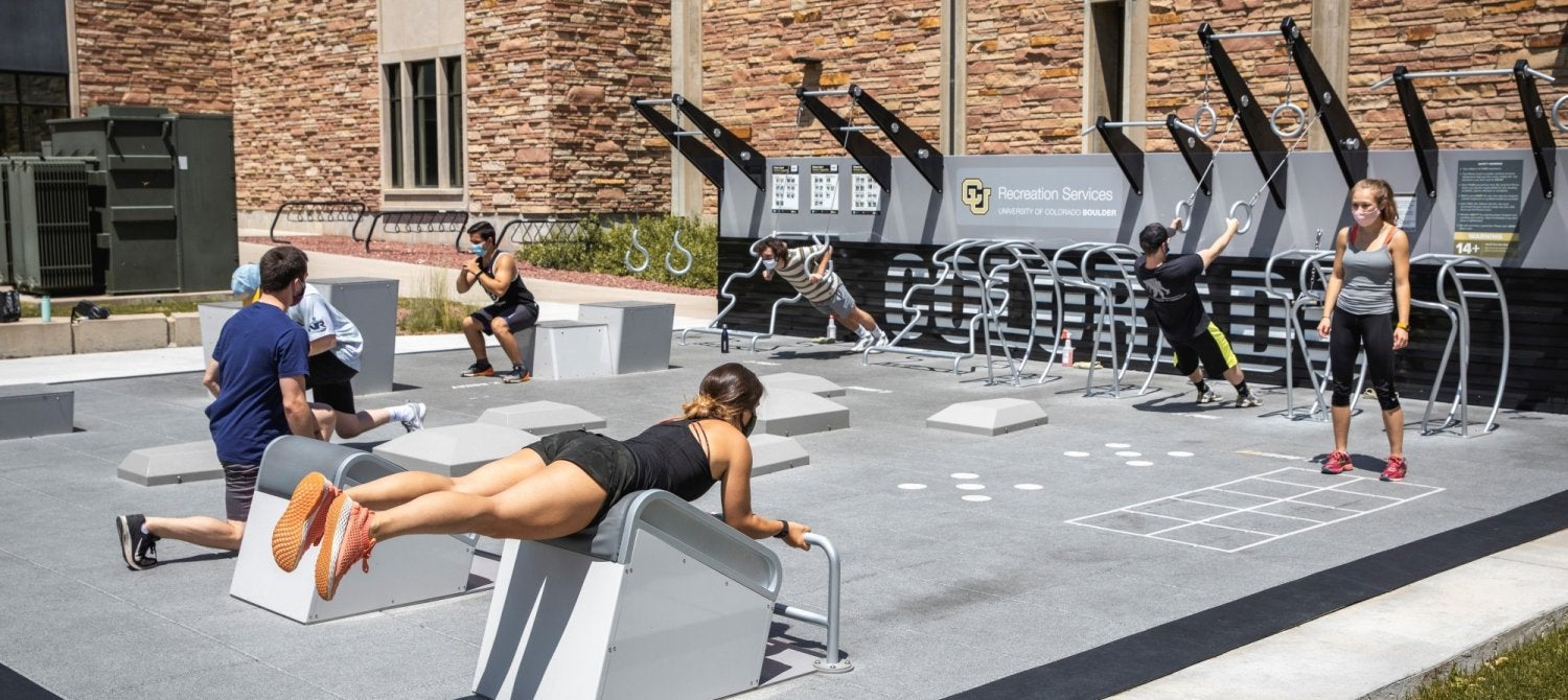 students in masks using the fitness courts