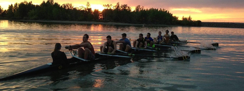 crew rowing on lake at dawn