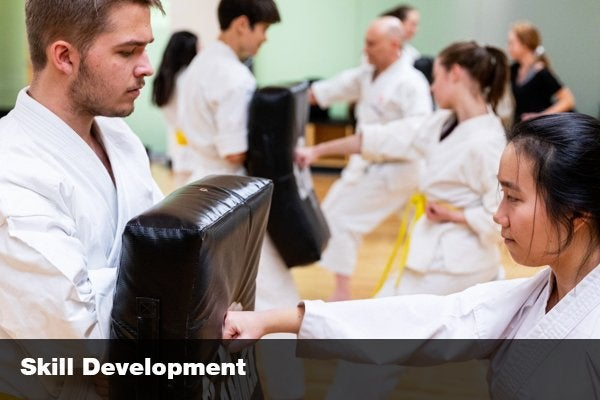 """student learning martial arts with the words """"skill development"""""""