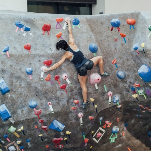 Female student bouldering in climbing gym