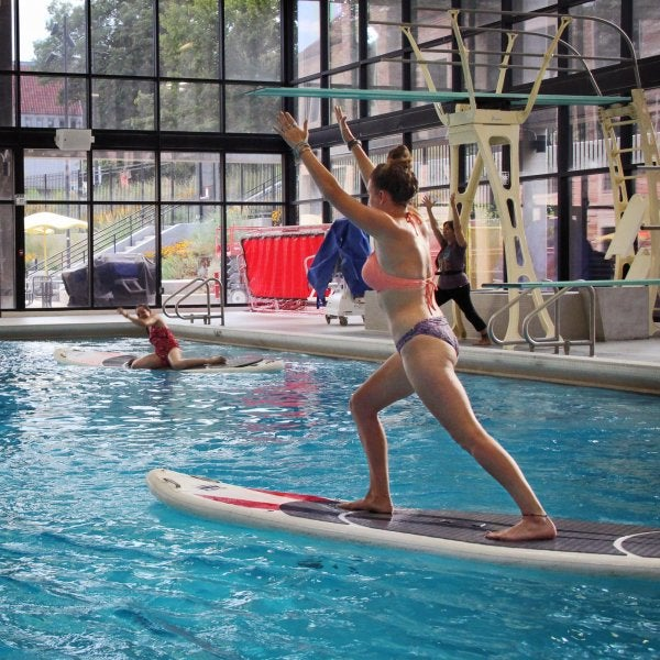 Person practicing yoga on a paddle board