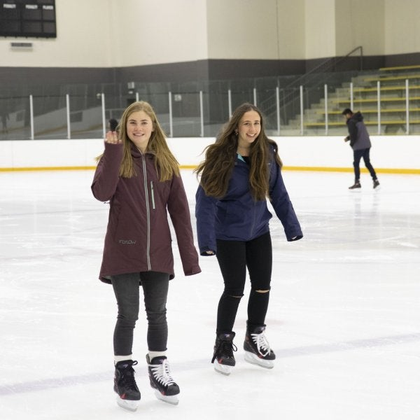 Two female students skating at the ice rink