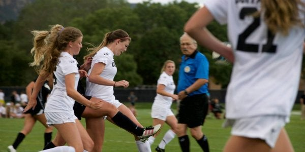 Women's soccer team passing ball