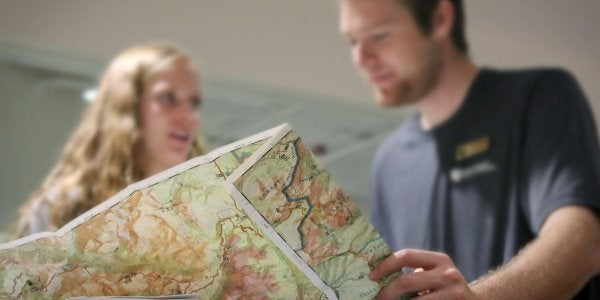 Adventure planning center of boy looking at map