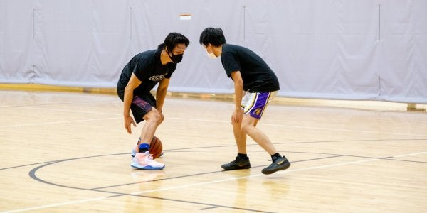 two students in masks playing basketball
