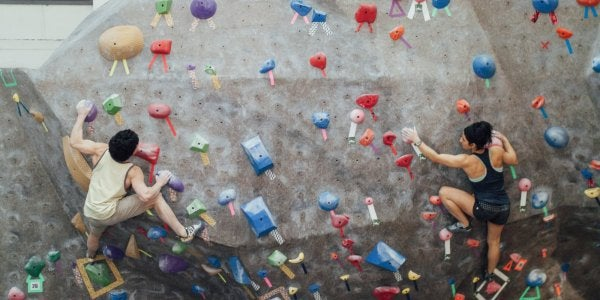 Two students bouldering at the Climbing Gym