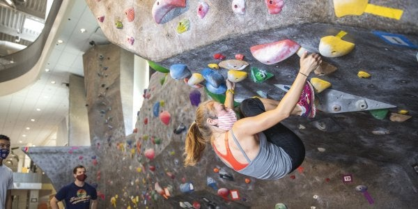 student using the climbing gym while wearing a face covering