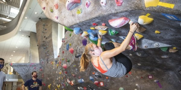 woman climbing in the climbing gym as someone coaches her on