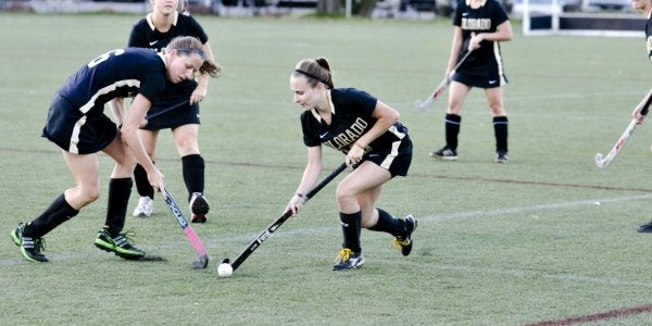 Students playing field hockey