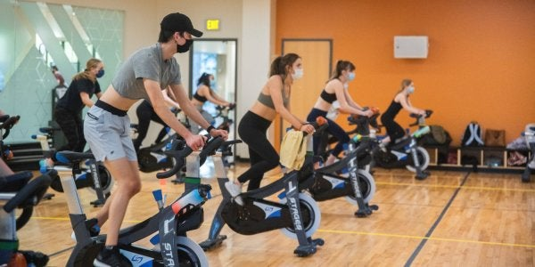 students in masks in the cycling studio