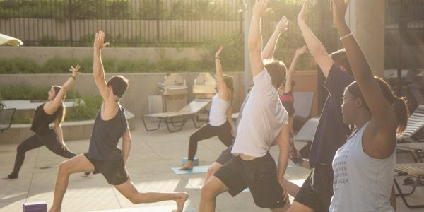 students doing yoga in the sunset