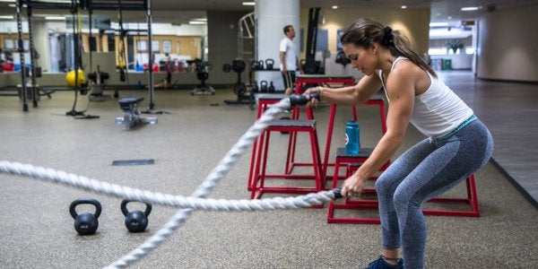 Female student using ropes in functional fitness area