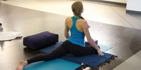 a woman stretches on a yoga mat