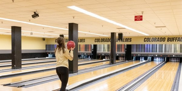 Girl preparing to throw a bowling ball down the lane at the connection