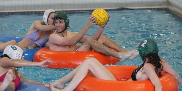 Students playing innertube water polo in the pool