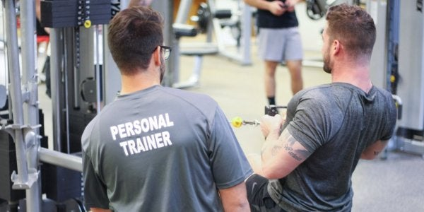 Personal trainer teaching student how to use seated row machine