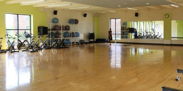 a large empty room with wooden floors and mirrored walls