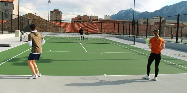 People playing doubles tennis
