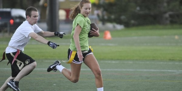 a woman with a football being chased on the playing field