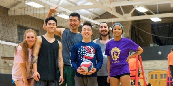 group of students posing next to a volleyball net